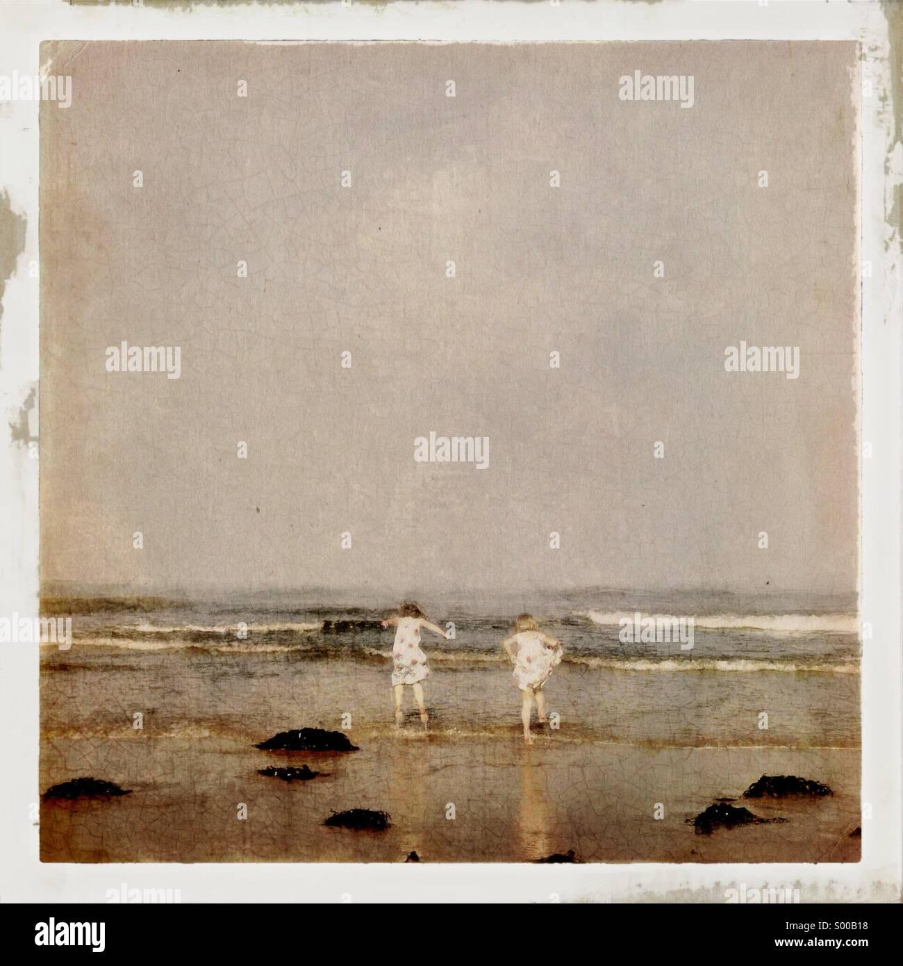 Glückliche Kinder springen und planschen im Meer am Abend in ihre Kleider Stockbild