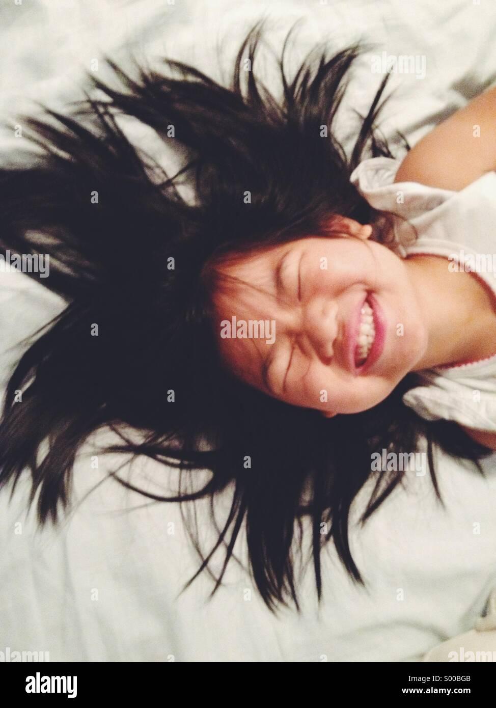 Junges Mädchen Bett lächelnd Handauflegen Stockfoto