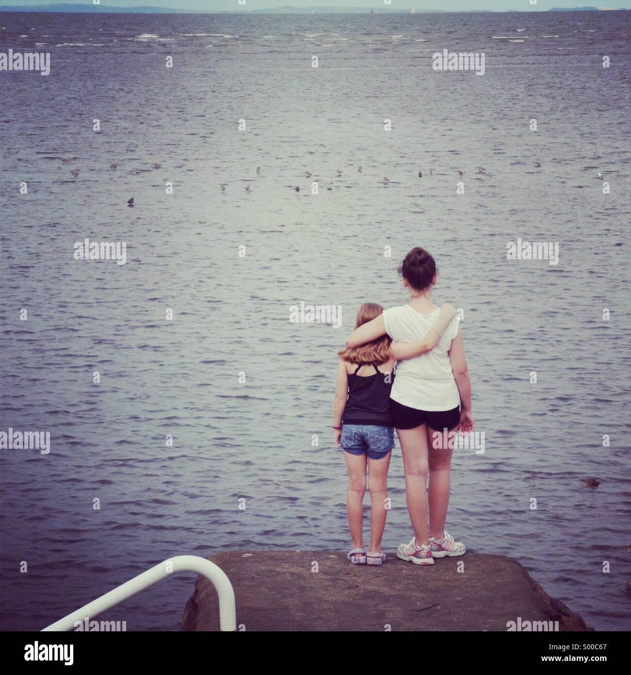 Zwei junge Mädchen umarmen am Meer. Stockbild