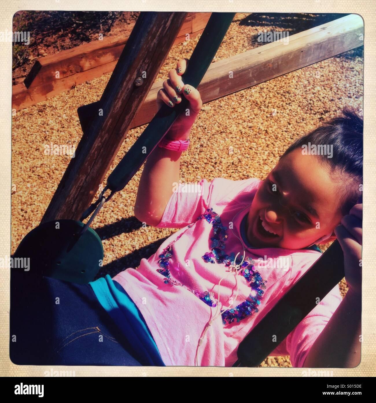 Kleines Mädchen Lachen auf Schaukel Stockbild