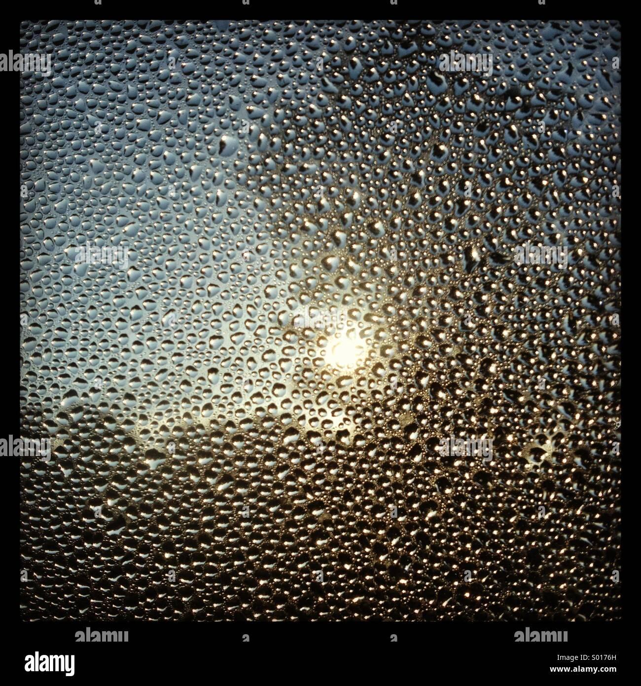 Kondensation in einem Fenster bei Sonnenaufgang Stockbild