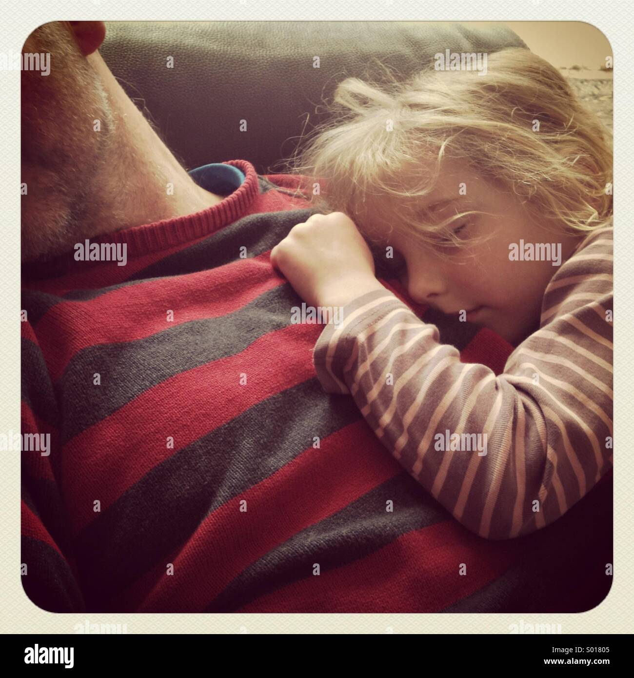 Eine Tochter schlief auf ihres Vaters Brust Stockfoto