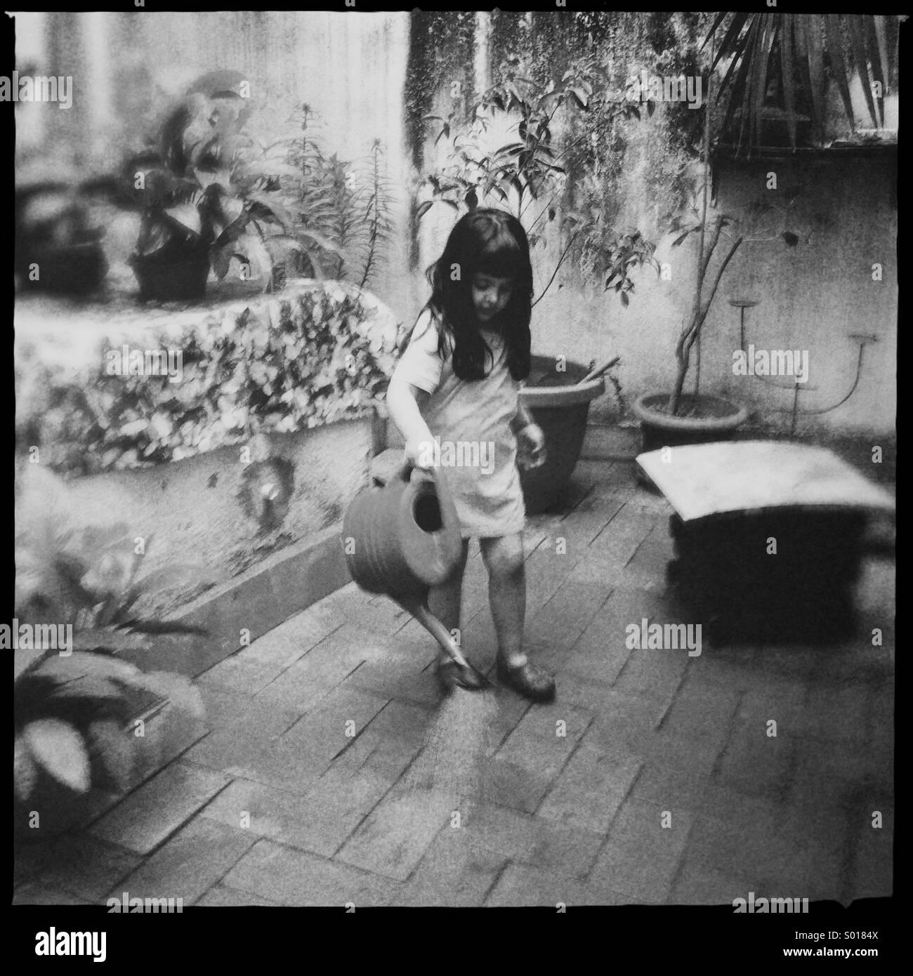 Mädchen spielen mit Wasser in ihrem Garten Stockbild