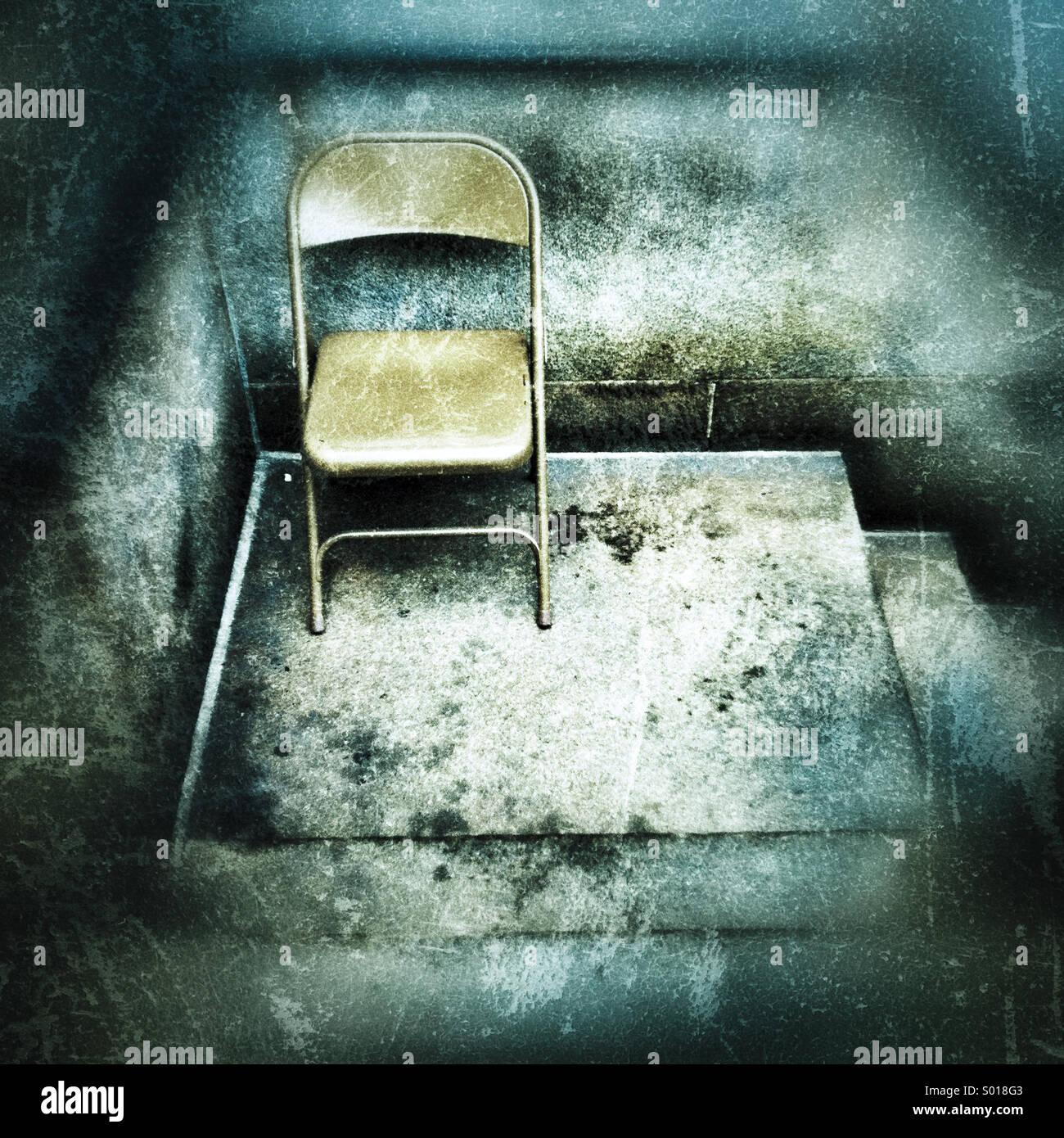 Ein Metall Klappstuhl sitzen auf einem notleidenden aussehende Zement stoop Stockbild