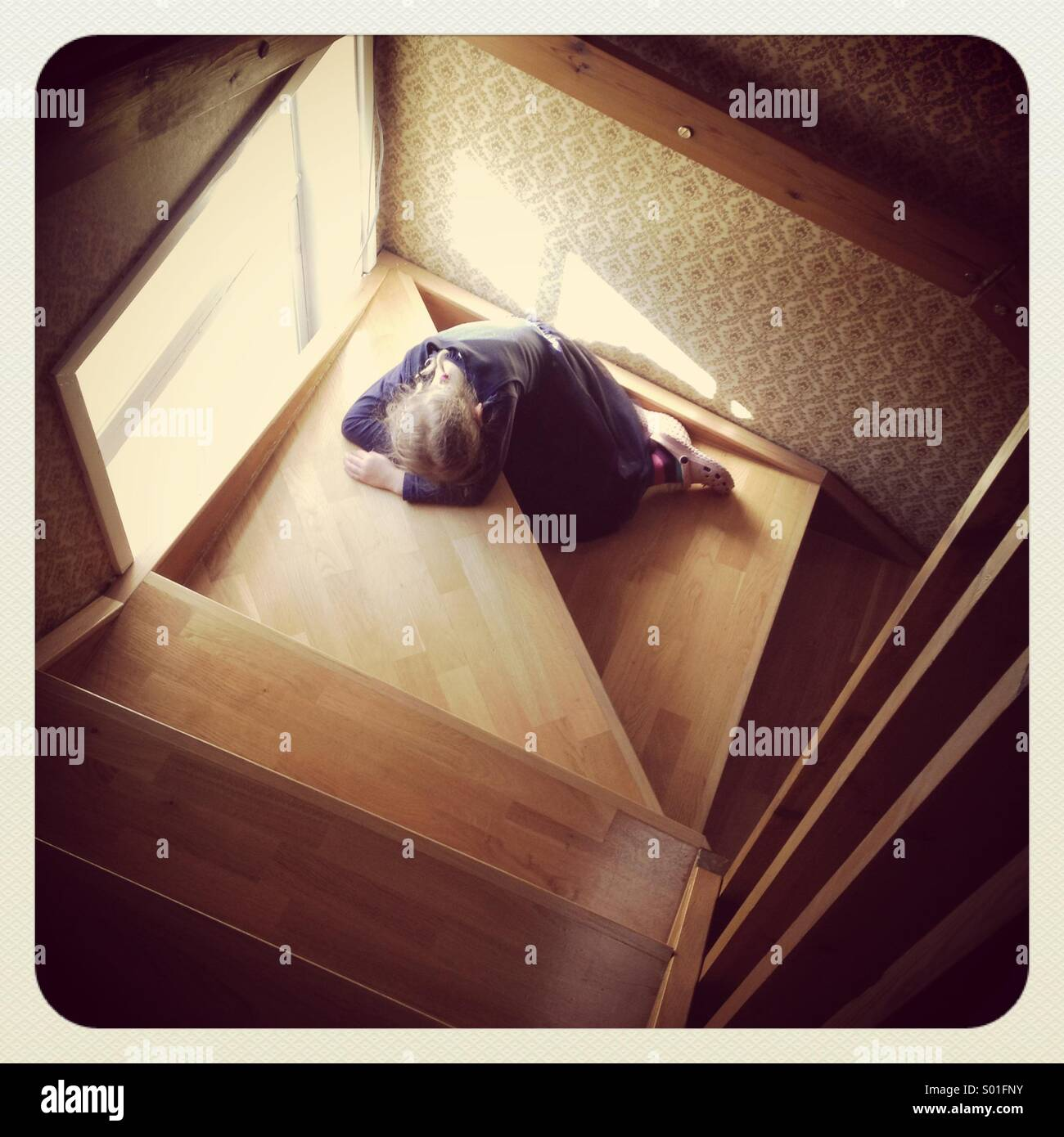 Ein junges Mädchen schlafend oder verärgert auf einige alte Holztreppen Stockbild
