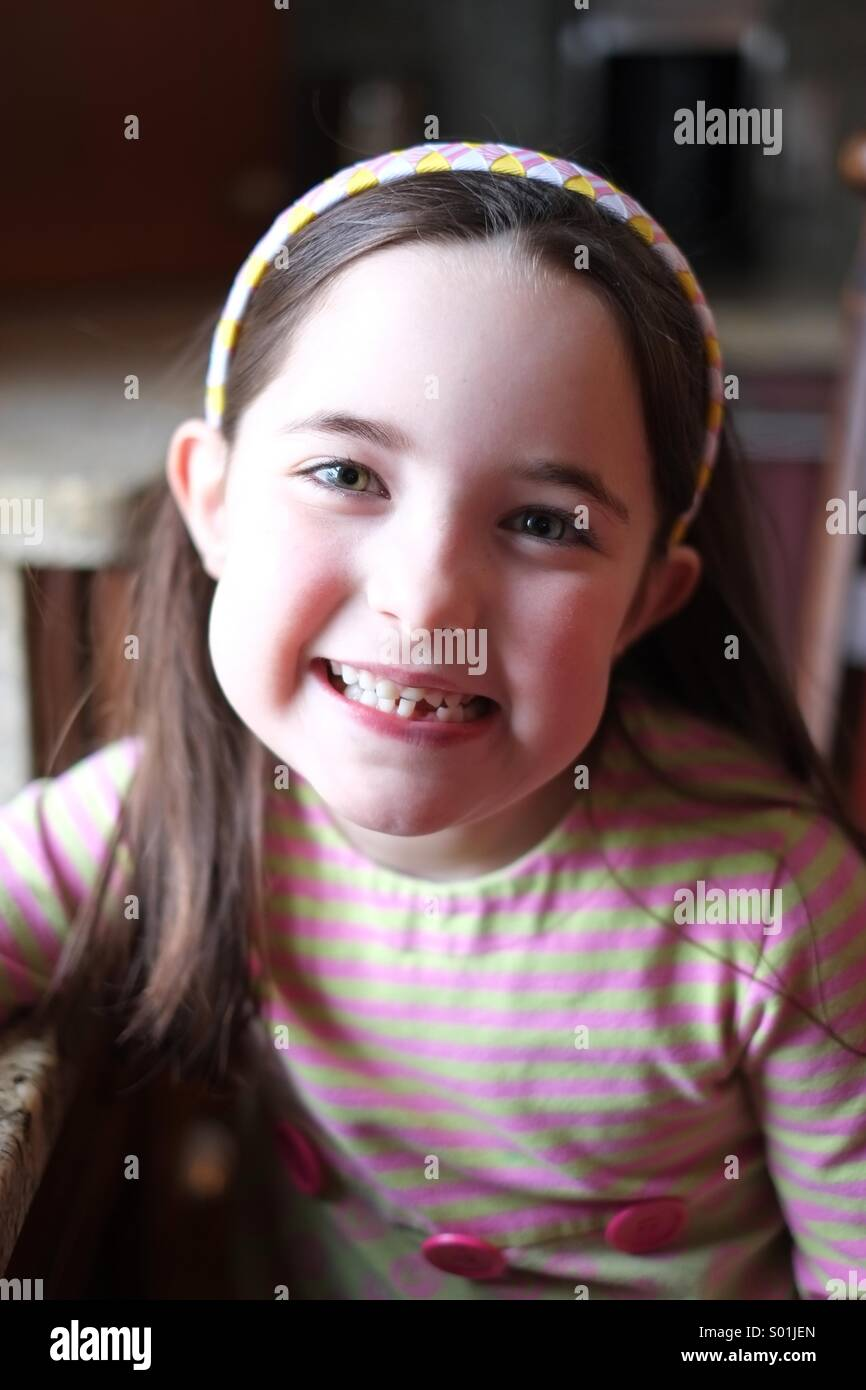 Lächelndes Mädchen verloren gerade ihren ersten Zahn. Stockbild