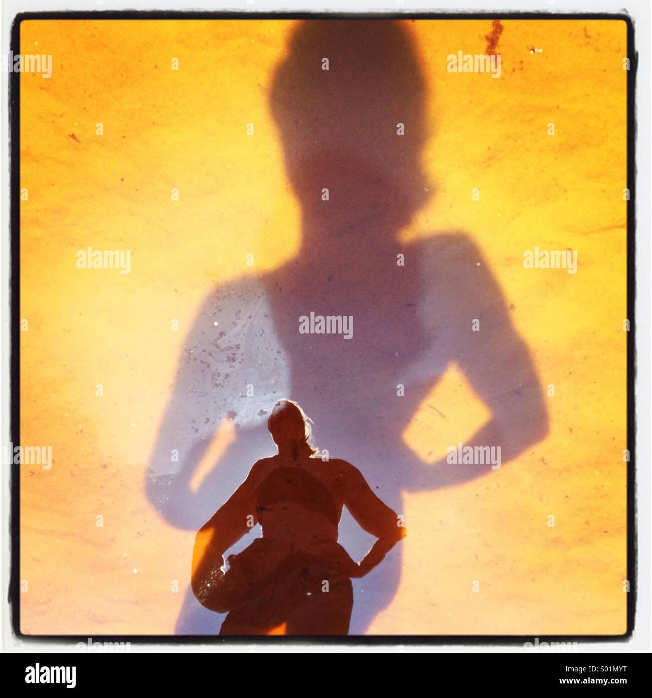 Eine mächtige Frau spiegelt sich in ihrem eigenen Schatten am Strand Stockbild