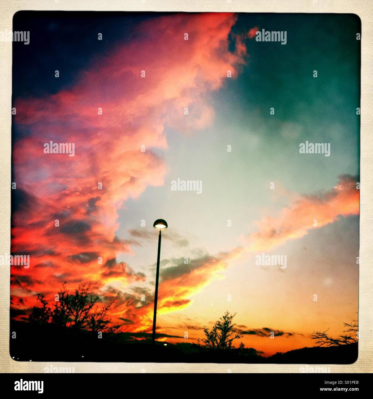 Einsamen Straßenlaterne gegen eine lebendige Sonnenuntergang Himmel. Stockbild