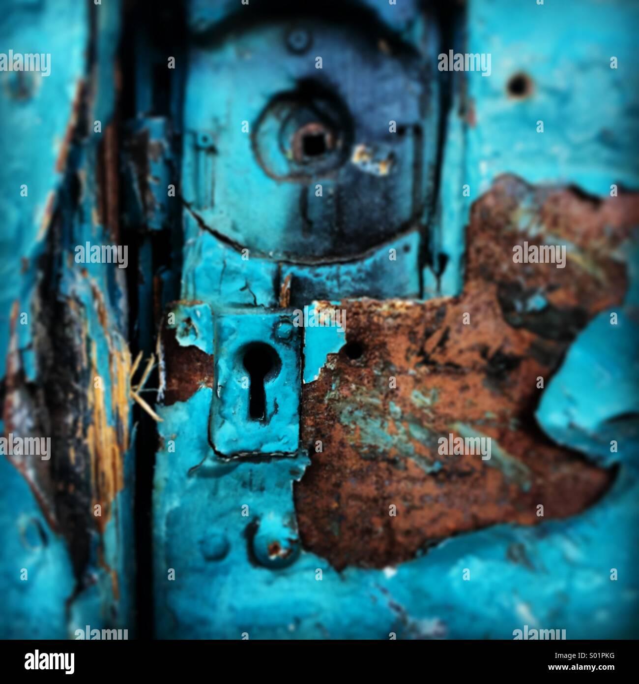 Rostigen alten heruntergekommenen gemalte blaue Tür mit kaputten Schloss. Stockbild