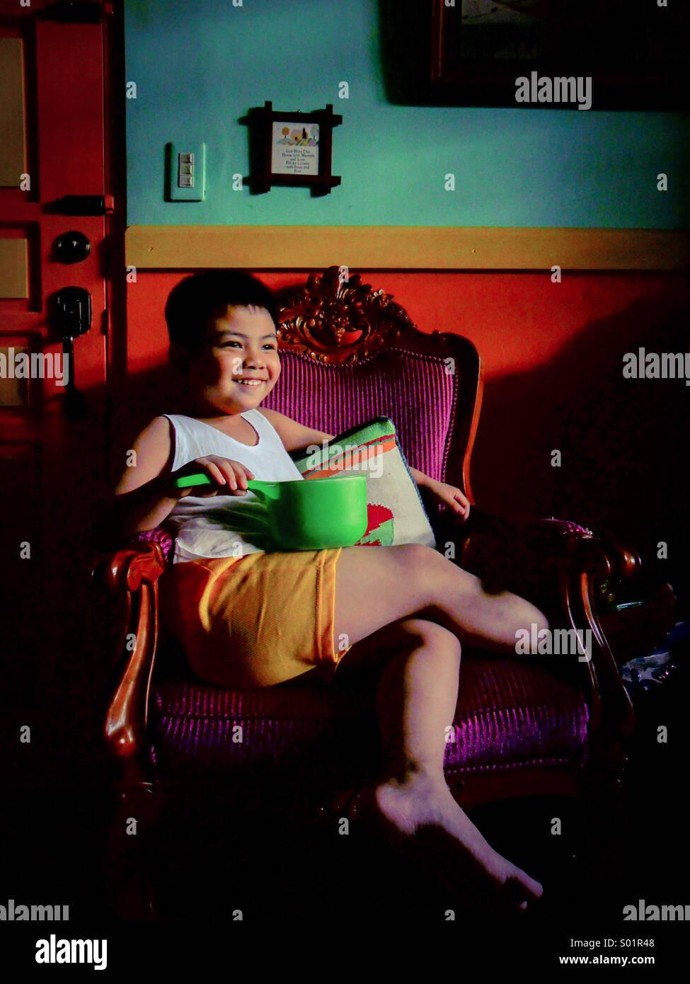 Asiatische junge sitzen auf einem Stuhl Stockfoto