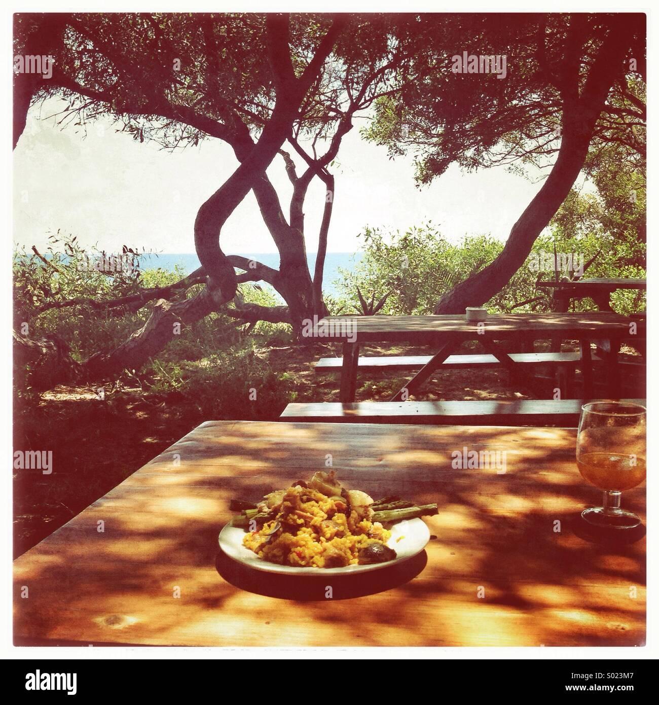 Mittagessen unter den Bäumen am Meer Stockbild