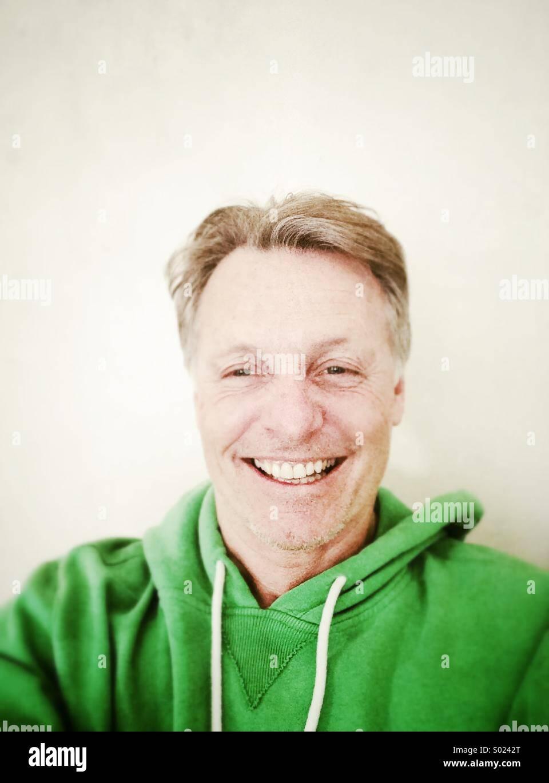 Glücklich lächelnd reifen Mann in seinen Vierzigern, trägt einen grünen Kapuzen Top. Stockbild