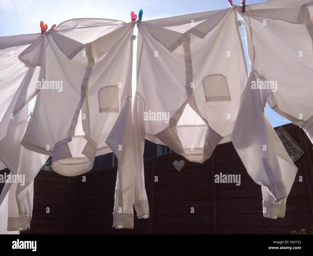 Weiße hemden auf einer wäscheleine in der sonne trocknen stockfoto
