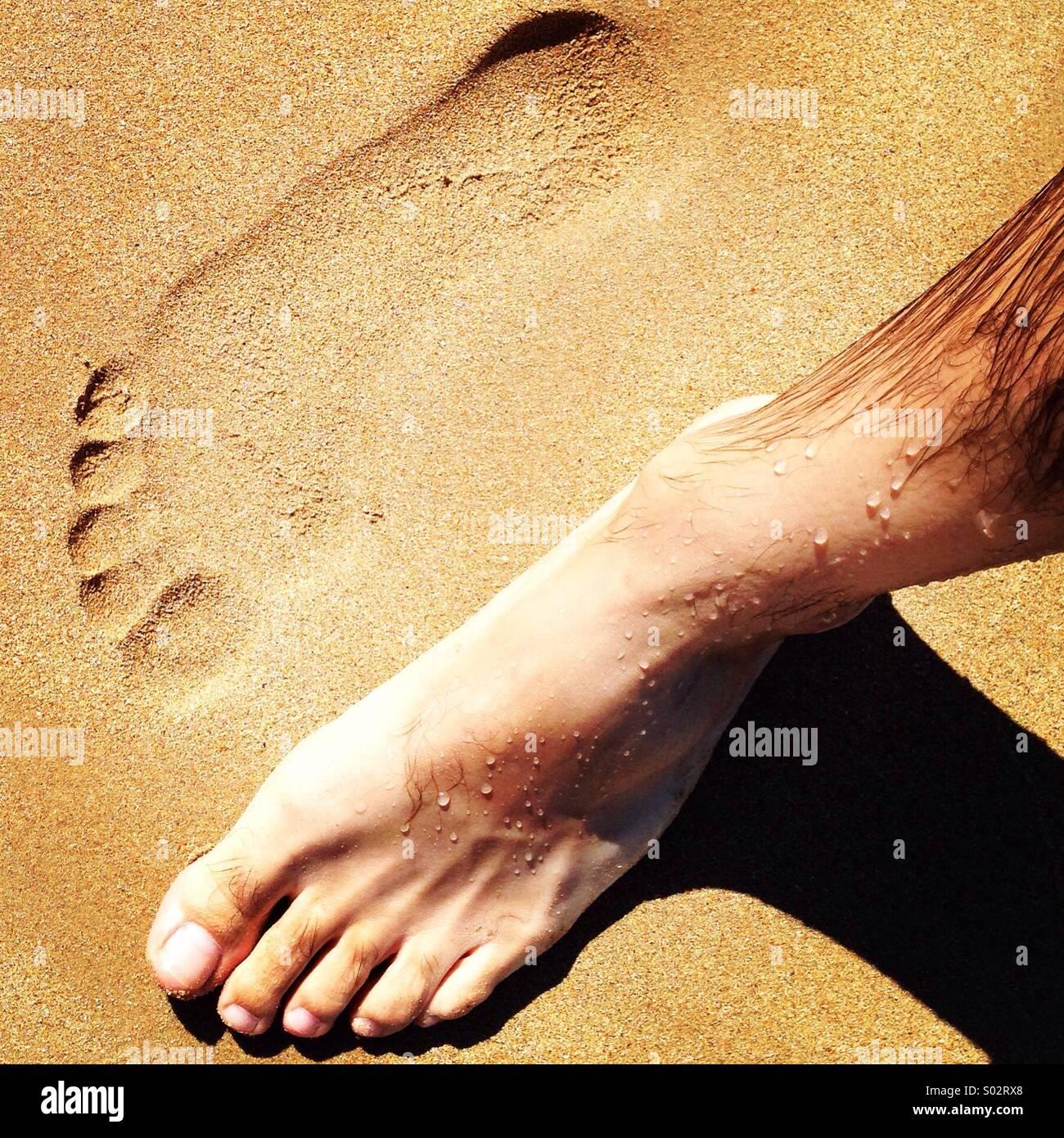 Linken Fuß und Fußabdruck auf sand Stockbild
