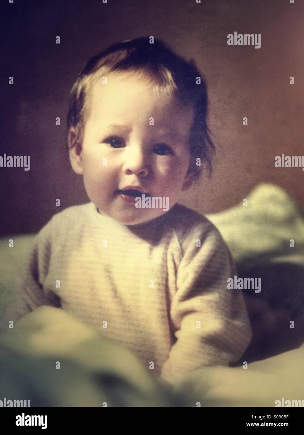 Baby im Alter von 9-12 Monaten sitzt auf Bett Stockbild
