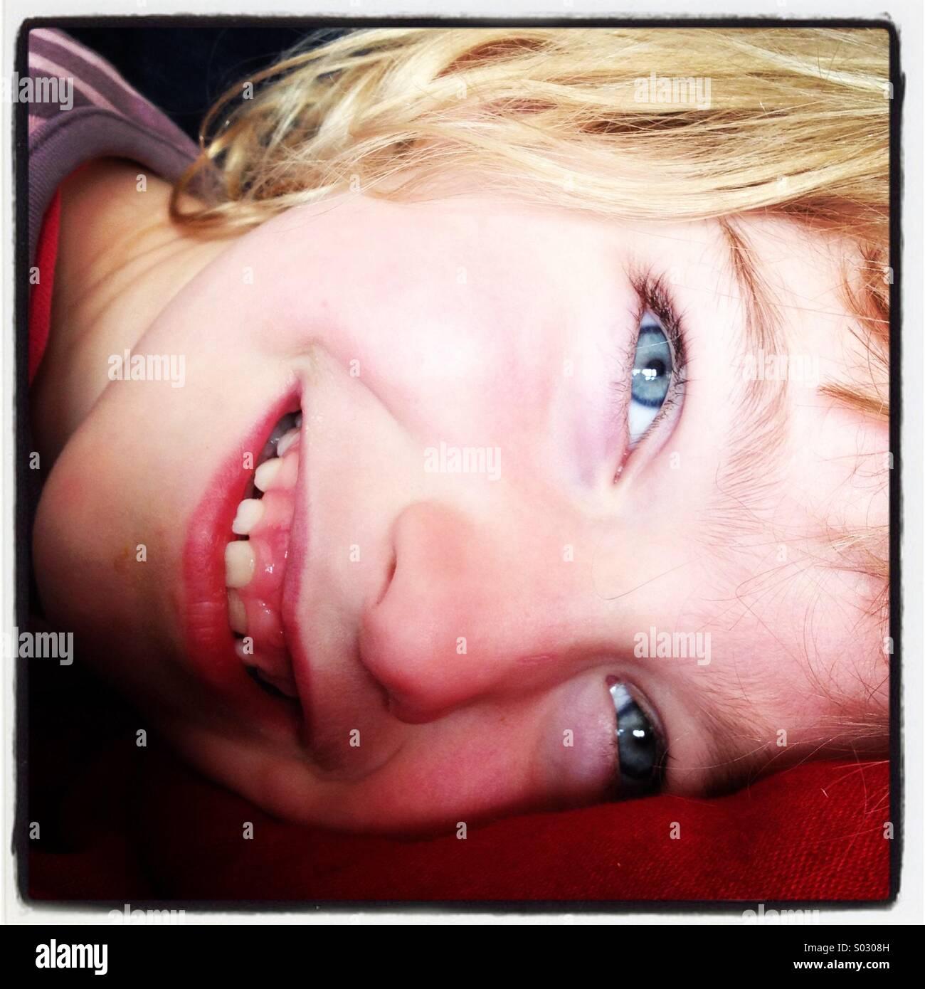 Ein Lächeln auf den Lippen freudig fröhliches Mädchen mit blauen Augen hinlegen... Stockbild