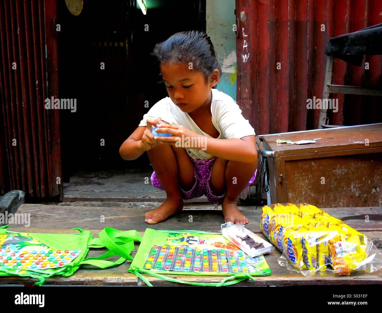 Junge asiatische Mädchen verkaufen Bonbons in Quiapo, Manila, Philippinen in Asien Stockfoto