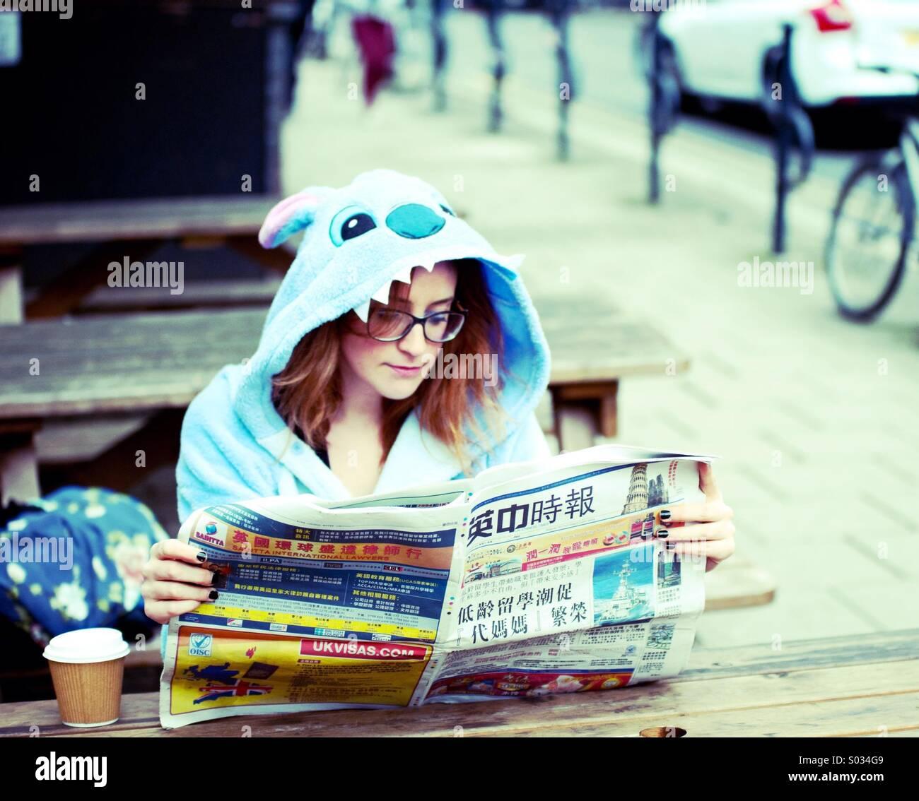 Frau in Stitch Kostüm eine chinesische Zeitung lesen Stockbild