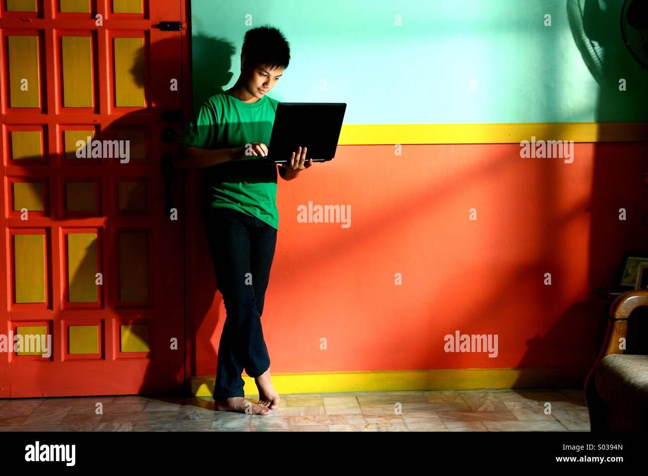 Junge Asiatische Teen Mit Einem Laptop Computer In Einem Leeren