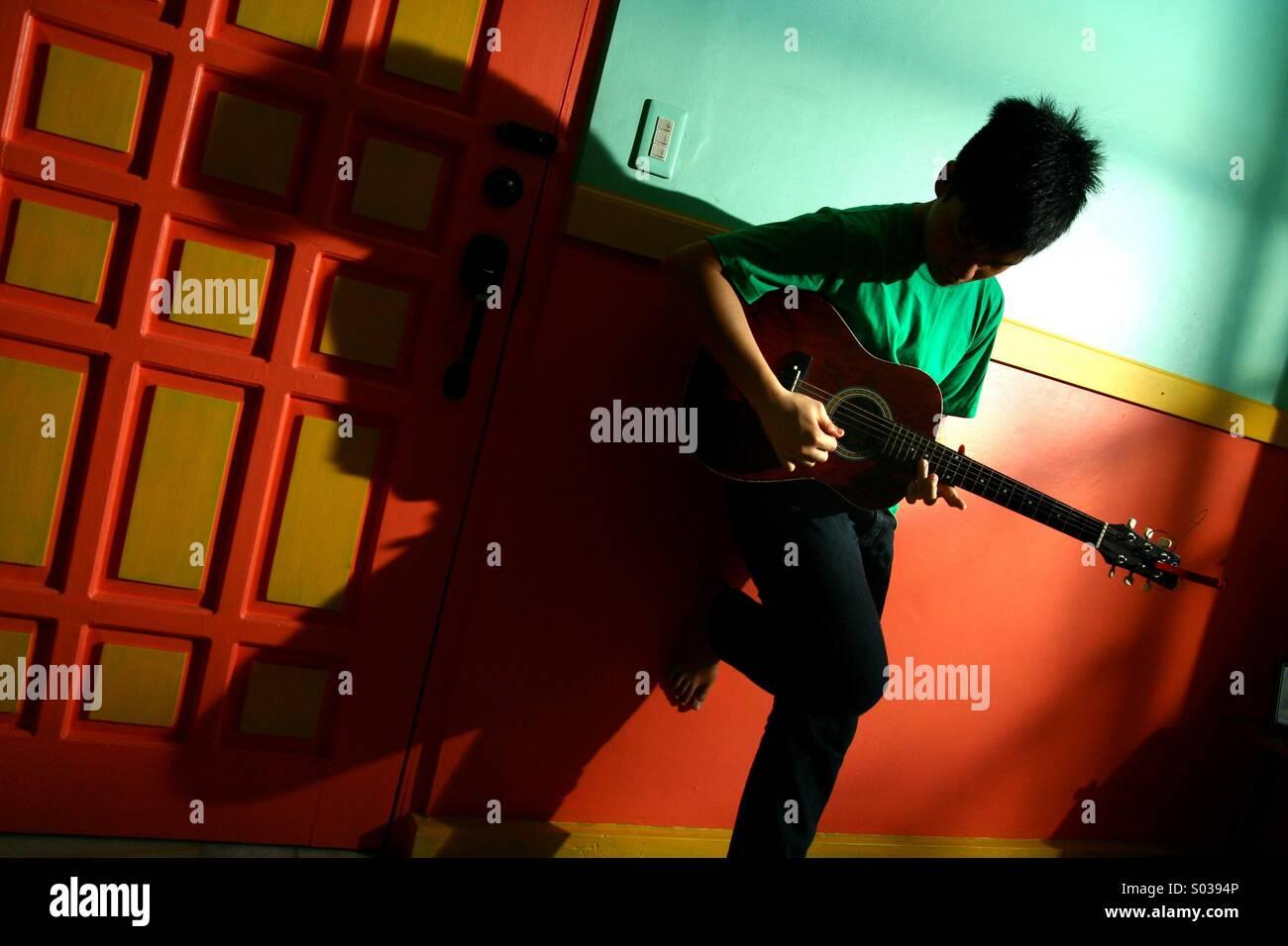 Junge asiatische Teen spielt Gitarre in einer leeren Wohnzimmer Stockbild