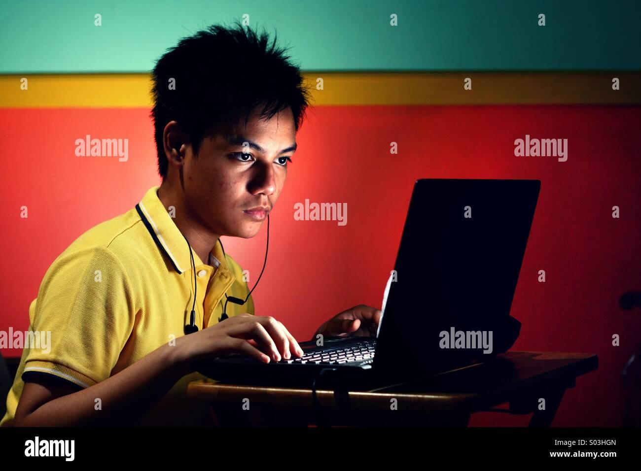 Asiatische Teenager Boy arbeiten oder studieren auf einem Laptopcomputer Stockbild