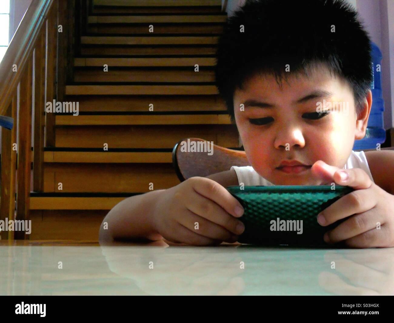 Junge asiatische Kind ansehen oder spielen auf einem Tablet Telefon Stockbild