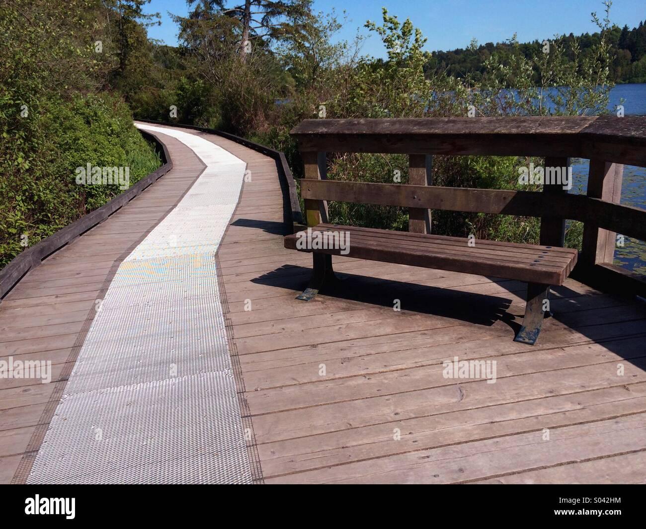Lovers Lane auf Holzsteg mit einer metallischen Oberfläche Anti-Rutsch - Pfad durch Wald an einem See Stockbild