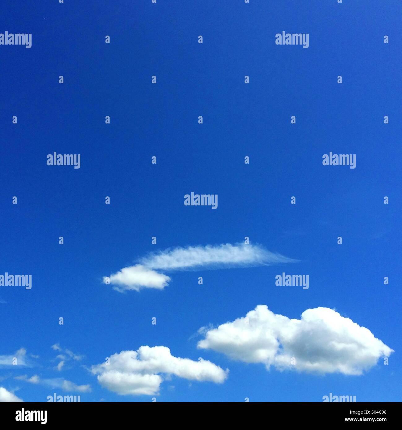 Flauschige Wolken gegen ein strahlend blauer Himmel Stockbild