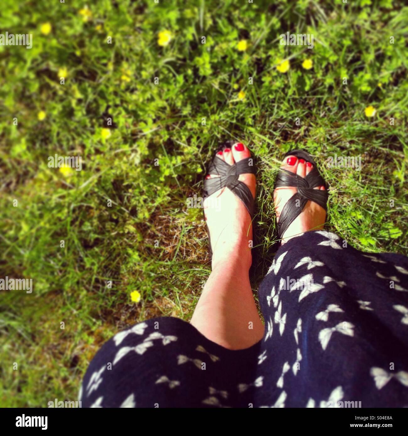 Blickte auf Füße in Sandalen und ein Sommerkleid, stehend auf einem LAN mit kleinen gelben Blüten Stockfoto