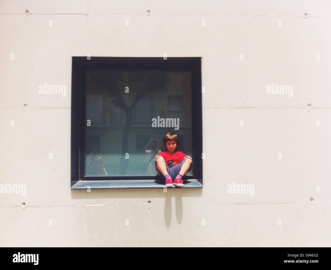 Junge sitzt auf einem Fenster Stockbild