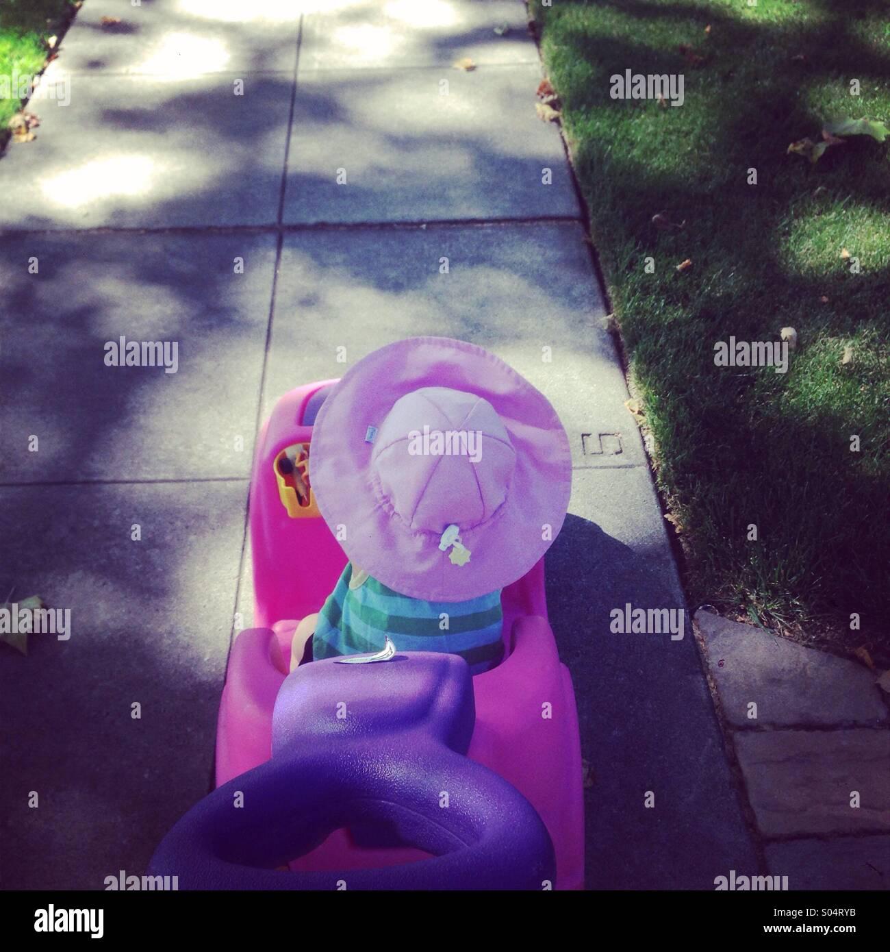Meine Tochter liebt es, in ihrem Auto um den Block jeden Tag spazieren gehen. Stockbild
