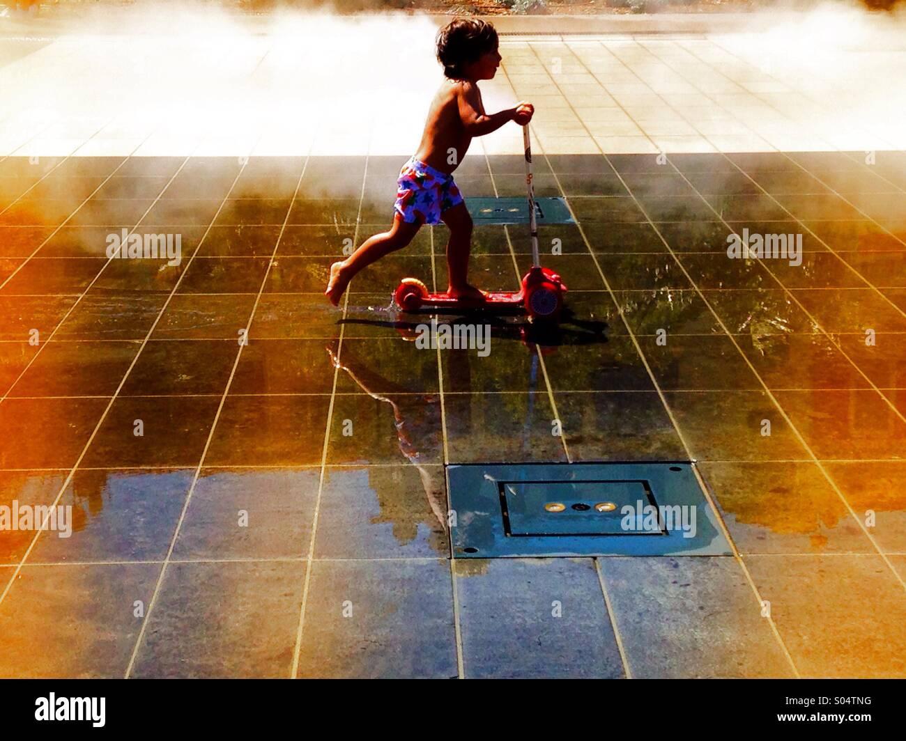 Kleiner Junge auf einem Roller Stockbild