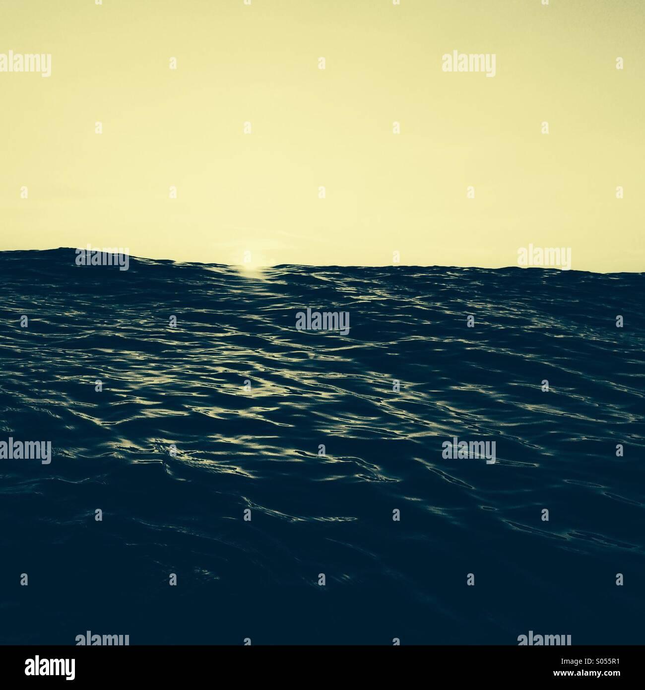 Erstes Licht in das Meer wie die Sonne am Horizont erscheint Stockbild