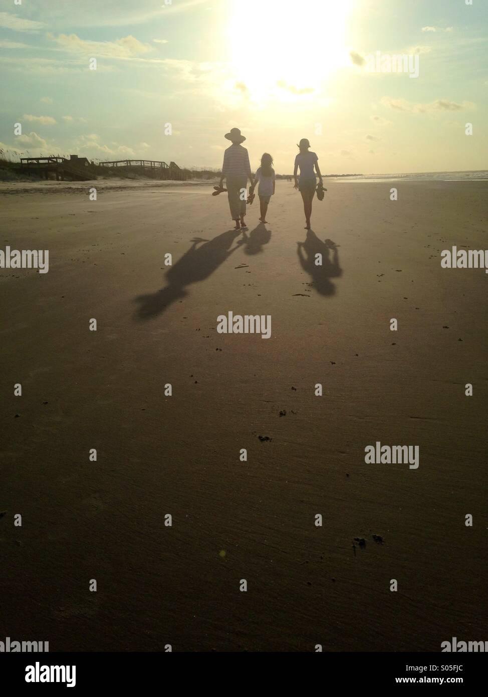 Die Silhouetten der drei Personen Fuß entlang des Strandes im Morgenlicht. Stockbild