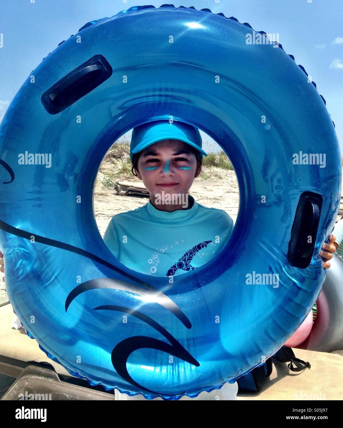 Ein süßes Kind in einen Hut hält eine blaue Innertube um ihr sunscreened Gesicht. Stockbild