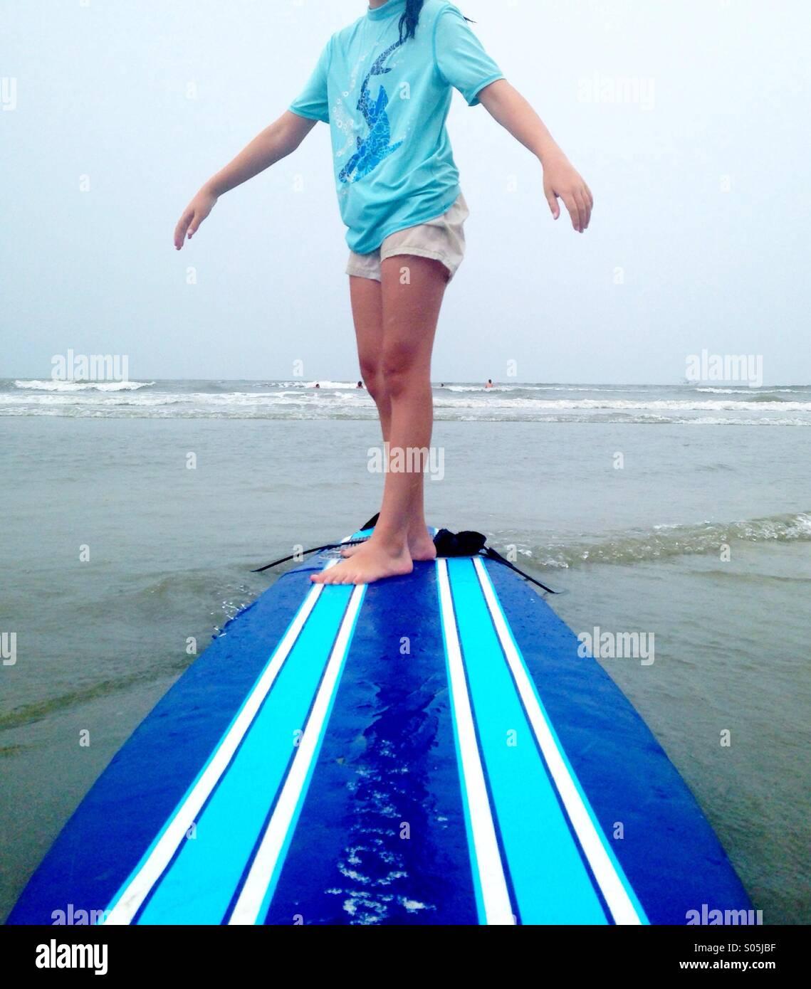 Ein Kind trägt ein Aqua Badeanzug steht auf einem gestreiften Surfbrett am Strand. Stockbild