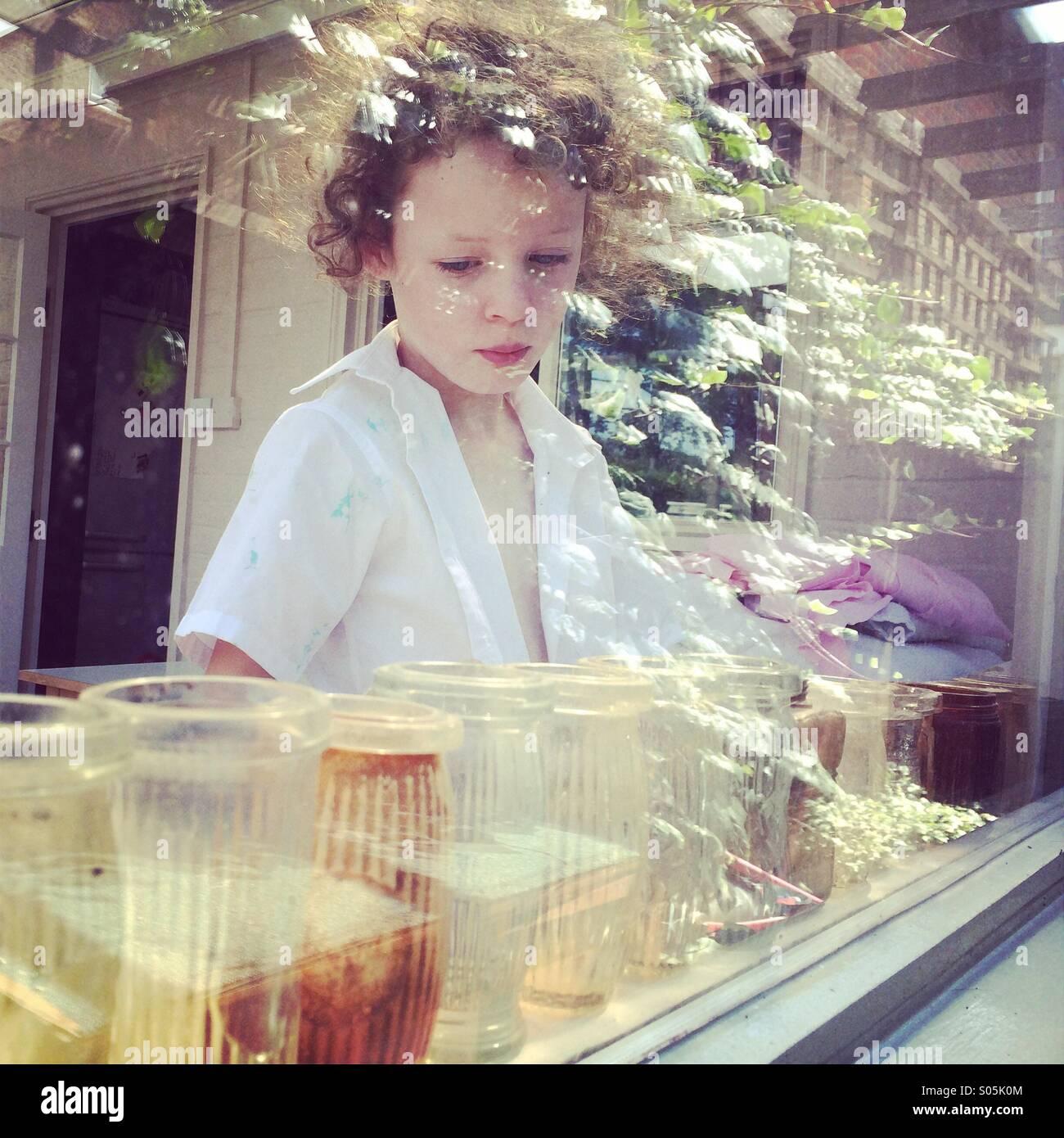 Nachdenklich Mädchen hinter Fenster mit Reflexionen Stockbild