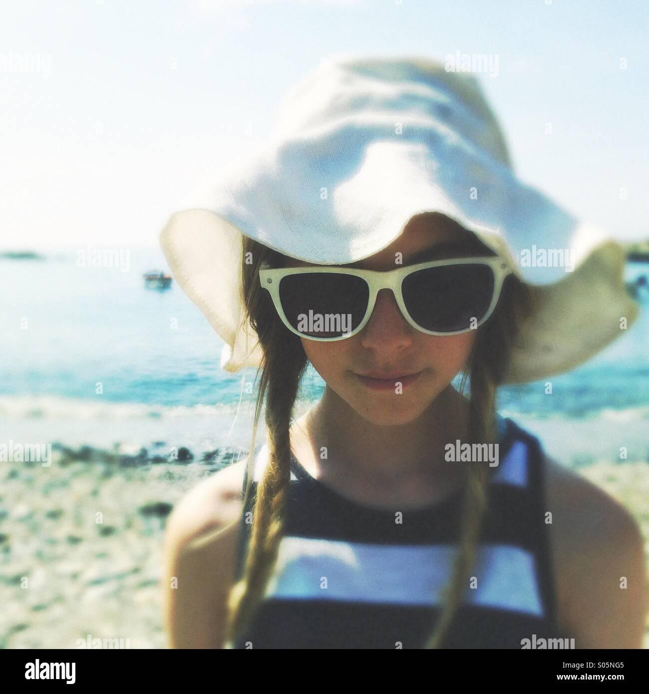 Teen Mädchen in Diskette mit Hut und Sonnenbrille am Strand Stockbild