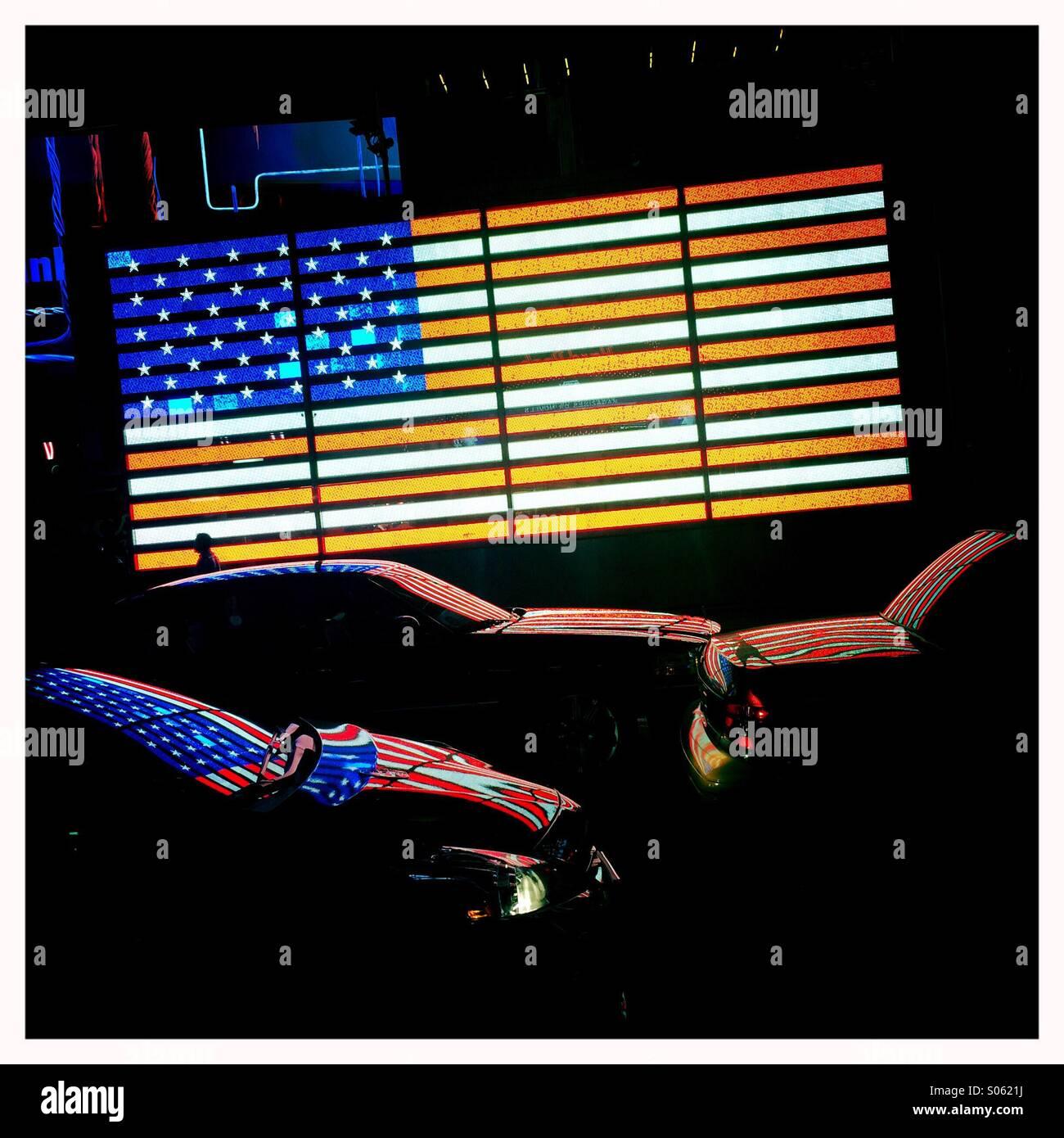 US-Flagge auf dem Times Square spiegelt sich im Verkehr Stockbild