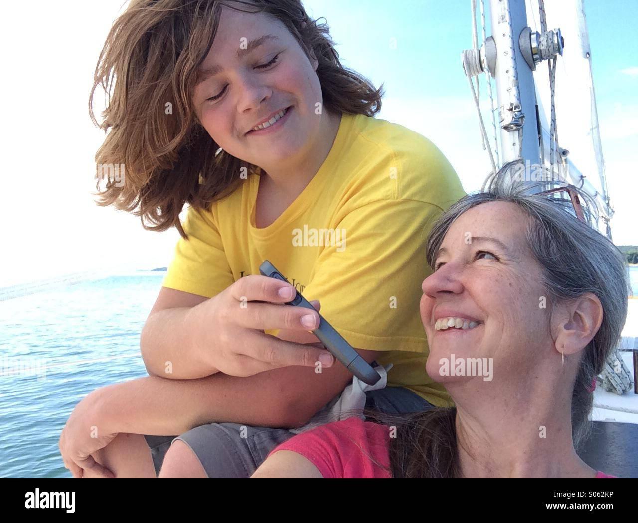 Teen und Mutter anhören von Iphone auf Boot Stockbild