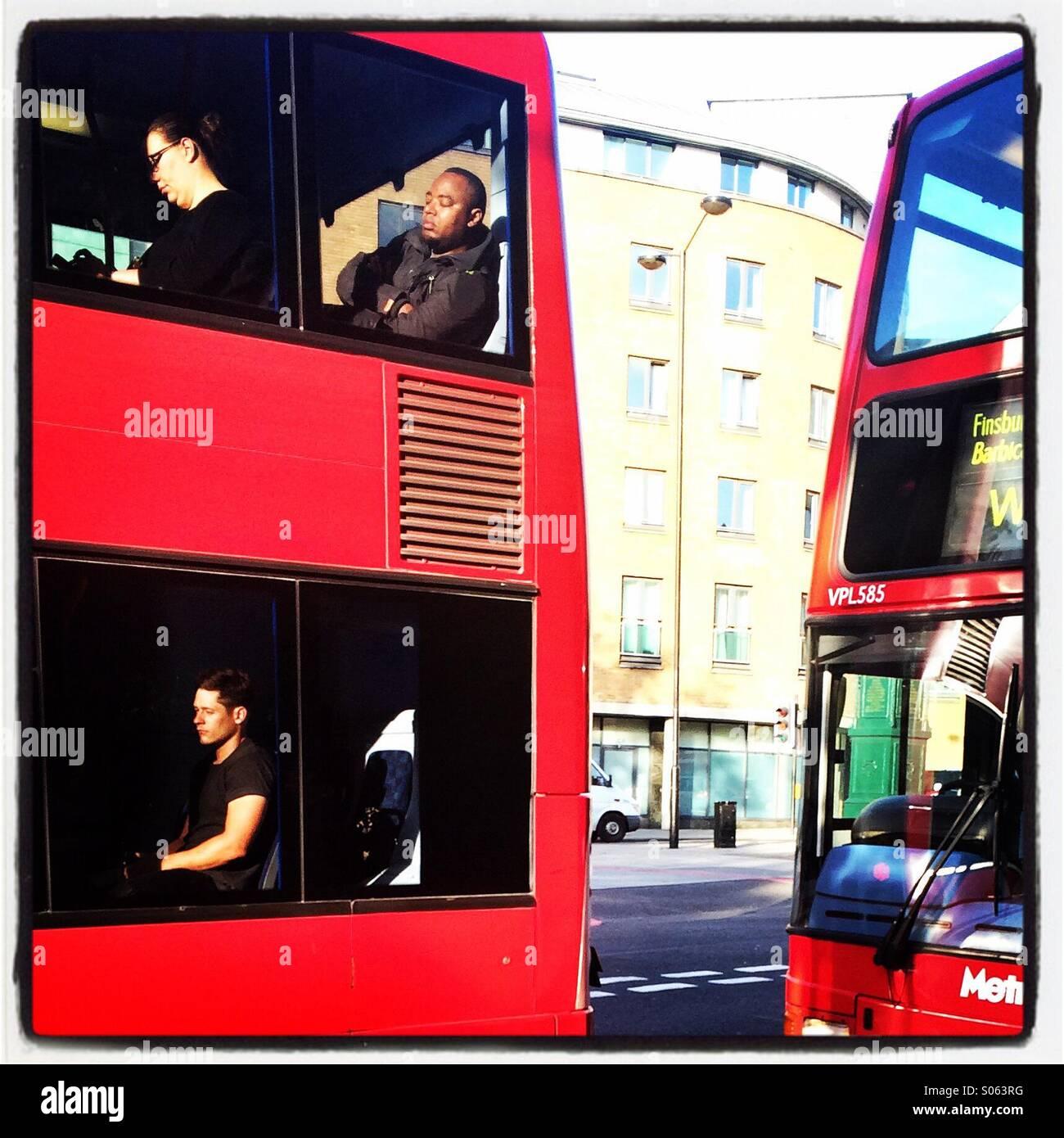 Menschen schlafen auf einem Londoner Bus. Stockbild