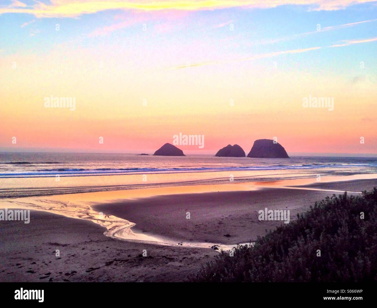 Felsen vor der Küste von Oregon in der Nähe von Cannon Beach sind gegen einen eindrucksvollen Sonnenuntergang Stockbild