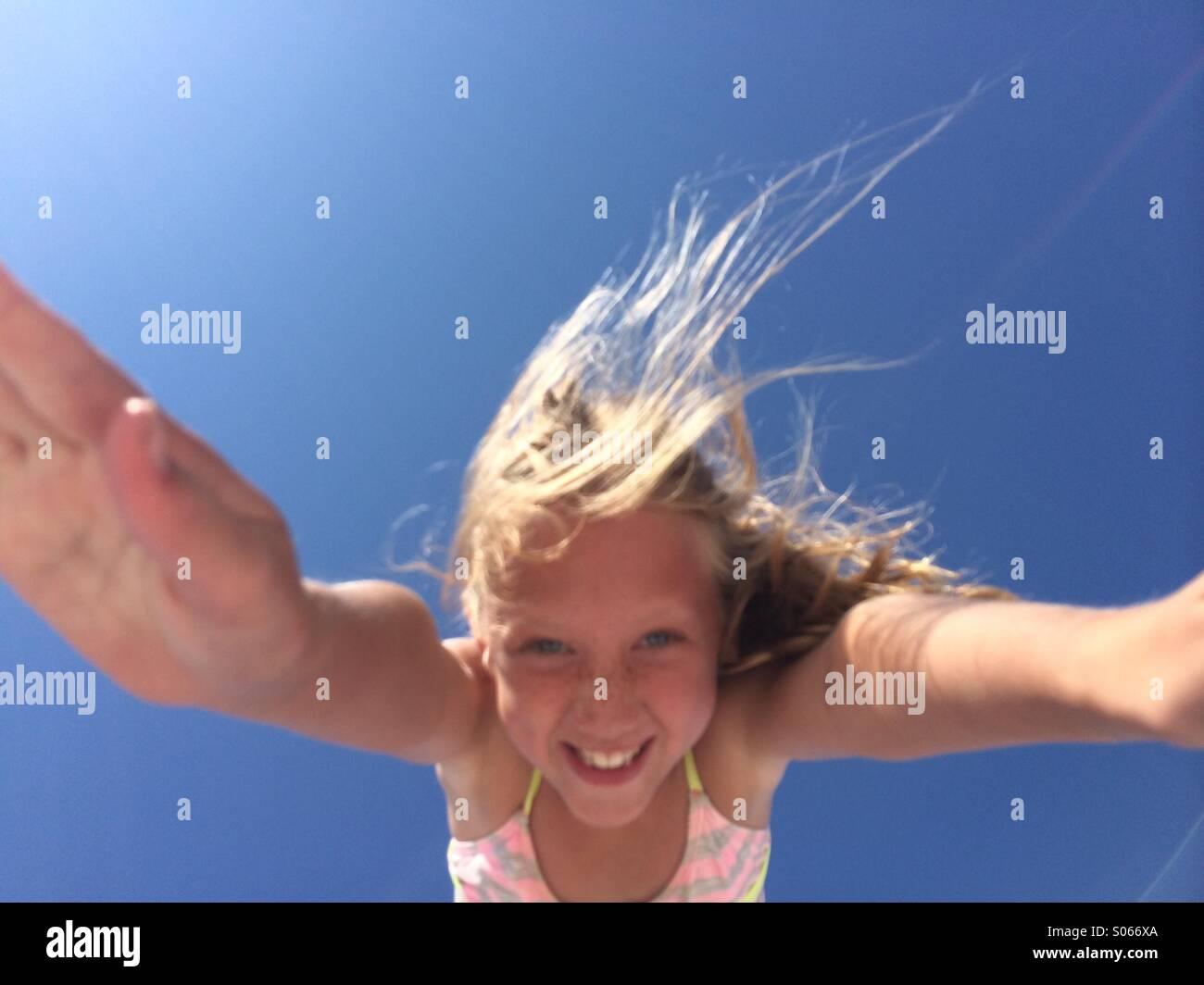 Mädchen mit den blauen Himmel dahinter in der Luft. Stockbild