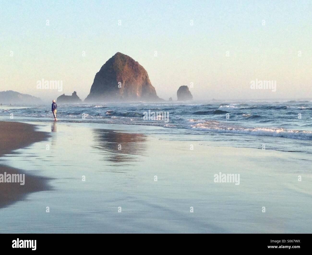 Ein Strand-Goer genießen einige Einsamkeit am Cannon Beach, Oregon in der Nähe von Haystack Rock. Stockbild