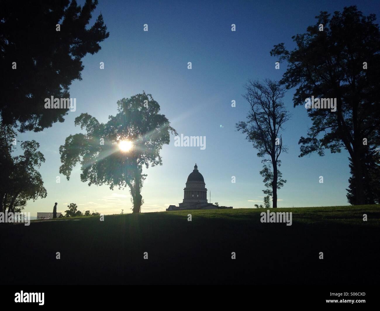 Die Sonne wird durch Bäume in einem Park in Salt Lake City gefiltert, die mit Blick auf das State Capitol Building. Stockbild