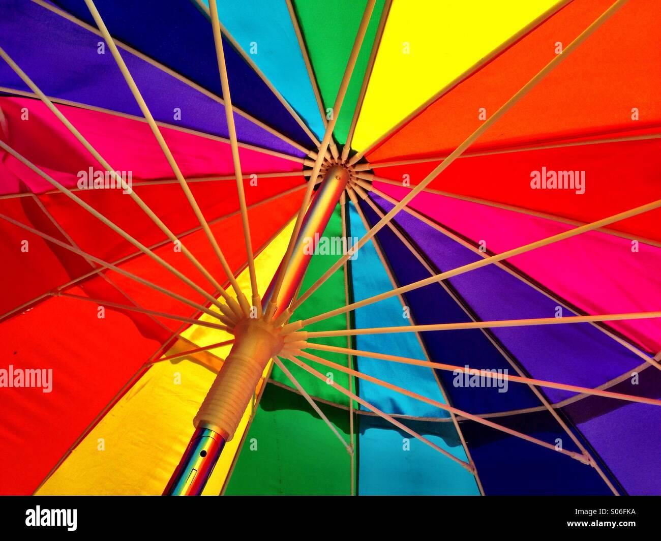 Ein regenbogenfarbenen Regenschirm leuchtet in der Sonne. Stockbild
