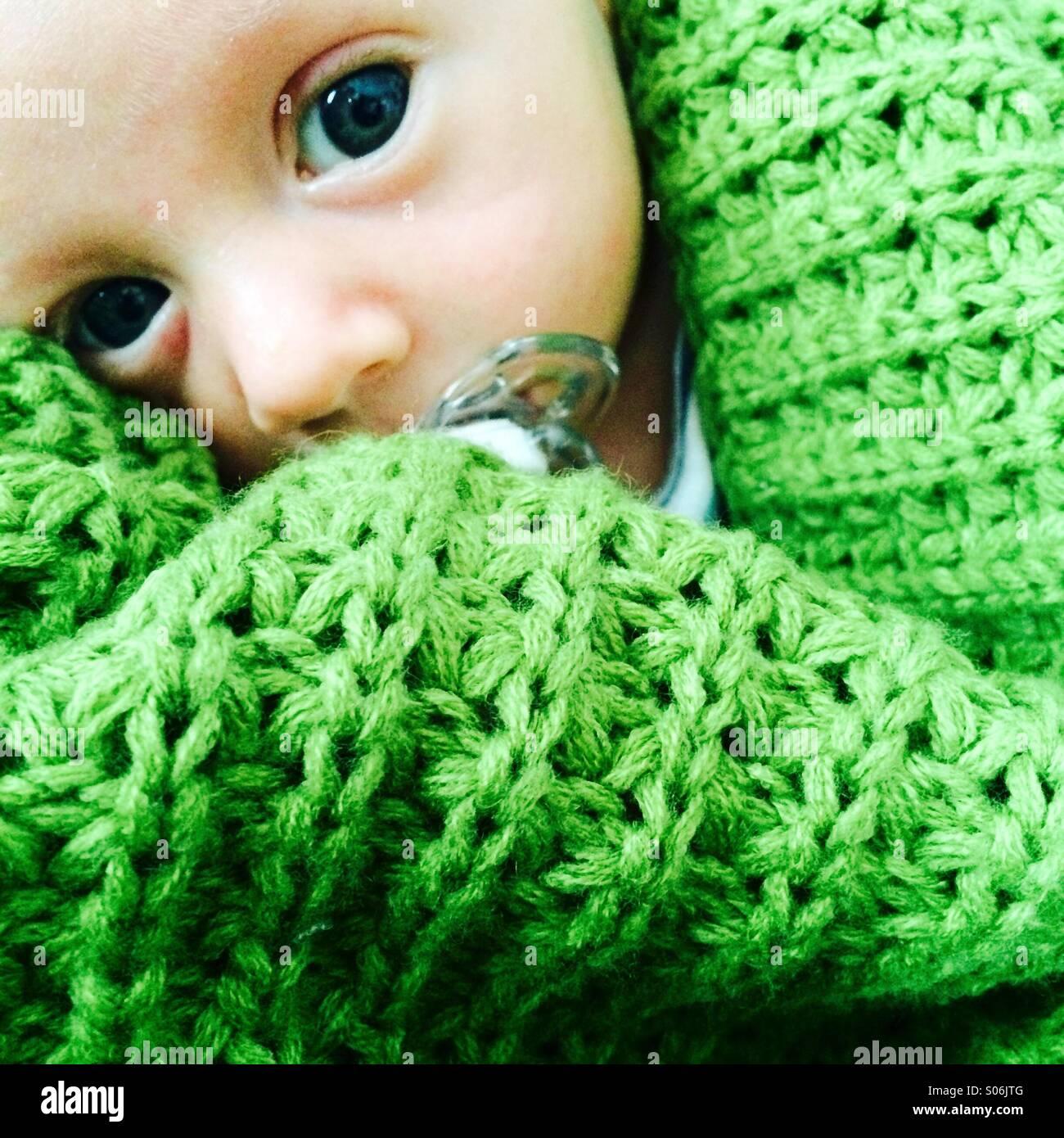 Ein Baby beruhigt durch eine Dummy-guckt heraus aus einer grünen Decke Stockbild