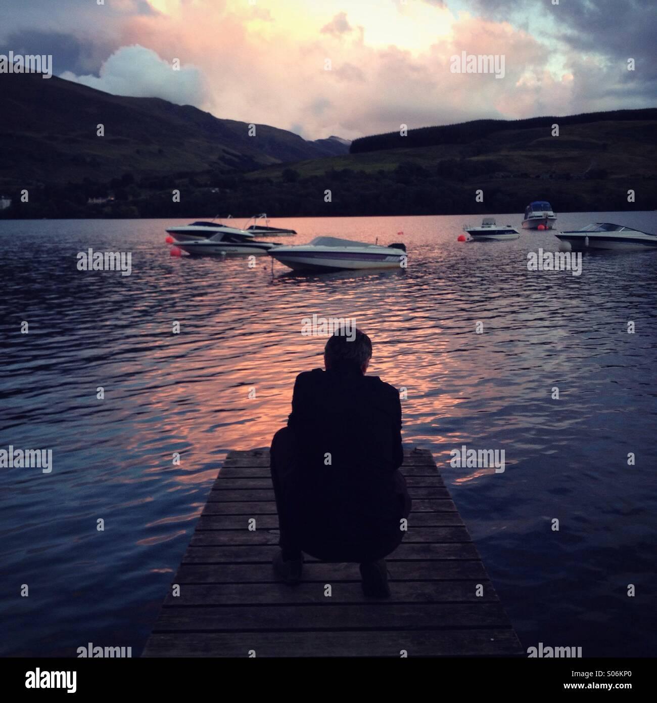 Ein hockender Mann Blick bei Sonnenuntergang auf einem schottischen loch Stockfoto