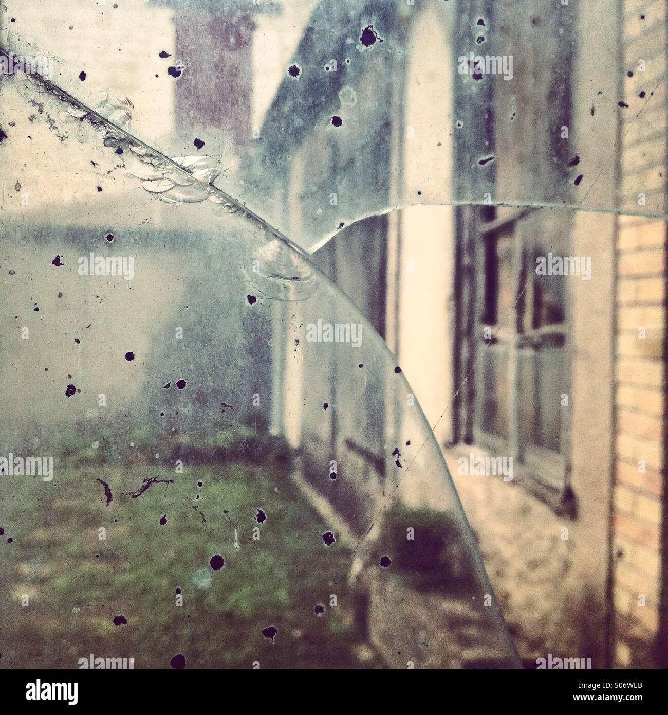 Eine alte Fassade durch ein zerbrochenes Glas betrachtet Stockbild