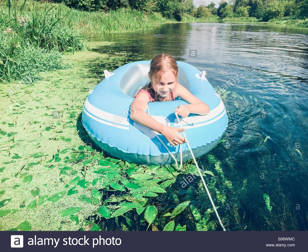 Kleines Mädchen sitzt in einem Floß auf einem reinen Fluss Stockbild